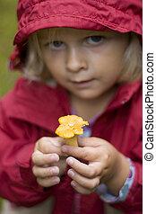 Little girl holding up a mushroom