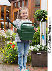 Little girl holding watering can while smiling - Little girl...