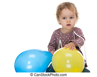 Little girl holding yellow and blue balloons