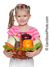 Little girl holds a basket with vegetables