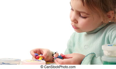 Little girl holds her made flower and wasp from plasticine