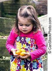 Little girl holds mandarin fruits