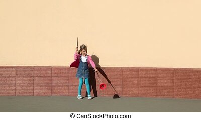 Little girl holds two sticks and plays toy near wall
