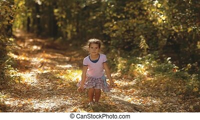 Little girl holds yellow leaves in the yellow autumn forest....