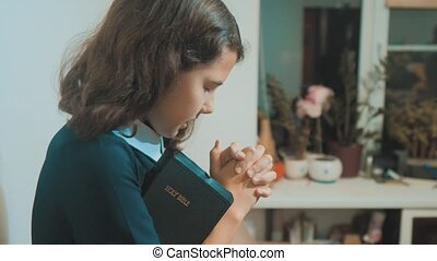 little girl holy bible prays with bible in her hands....
