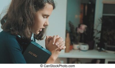 little girl holy bible prays with bible in her hands...