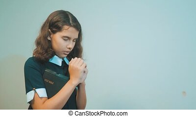little girl holy bible prays with bible in her hands. the...