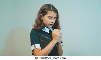 little girl holy bible prays with bible in her hands. the catholicism sacred holy bible. children and religion upbringing faith symbol. Little girl with praying. Peace, lifestyle hope, dreams concept