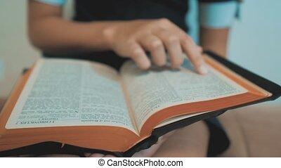 little girl holy bible prays with bible in her hands. the catholicism sacred holy bible. children and religion lifestyle upbringing faith symbol . Little girl with praying . Peace , hope, dreams concept