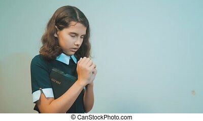 little girl holy bible prays with bible in her hands. the catholicism sacred holy bible. children and religion upbringing faith symbol. Little girl with praying. lifestyle Peace , hope, dreams concept