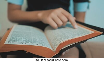 little girl holy bible prays with bible in her hands. the catholicism sacred holy bible. children and religion upbringing lifestyle faith symbol . Little girl with praying . Peace , hope, dreams concept