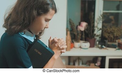 little girl holy bible prays with bible in her hands. the catholicism sacred holy lifestyle bible . children and religion upbringing faith symbol . Little girl with praying . Peace , hope, dreams concept