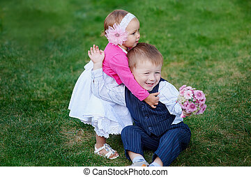 Little girl hugging a boy with a bouquet of flowers in park