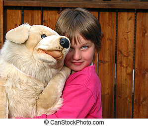 Little girl hugging a bug plush toy dog - Little girl...