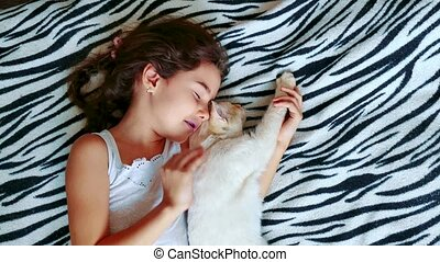 little girl hugging a cat lying on the bed. girl and pet...