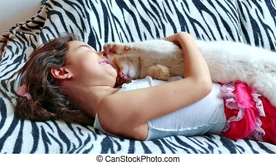 little girl hugging a cat lying on the bed. girl and pet white cat friendship care love. girl and cat concept lifestyle