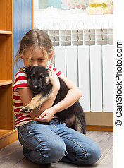 little girl hugging a puppy German Shepherd
