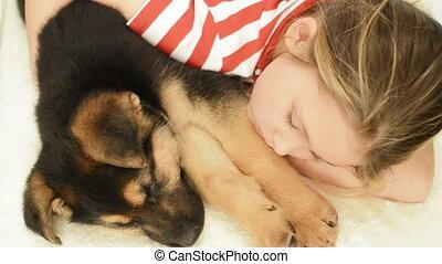 little girl hugging a puppy sleepin