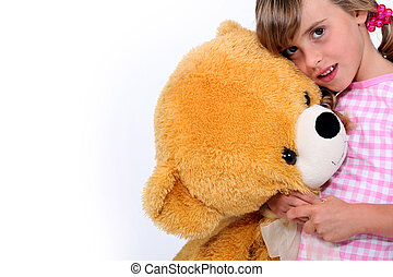 Little girl hugging a teddy bear
