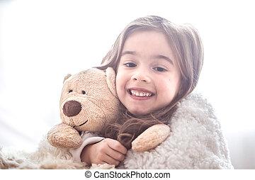 Little girl hugging bear toy on light background