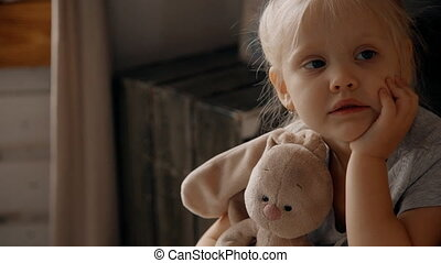 Little girl hugging her teddy toy. Beautiful female child...