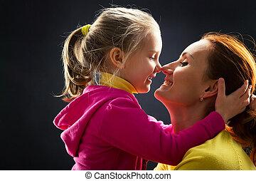 Little girl hugs her mother