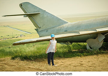 Little girl in a baseball cap at the airport near the old military aircraft.