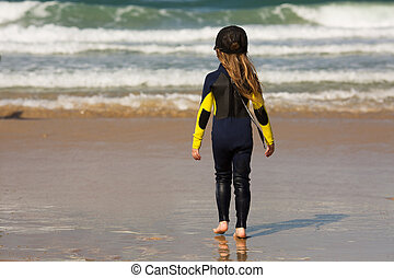 little girl in a cap and a surfer suit is standing on the ...