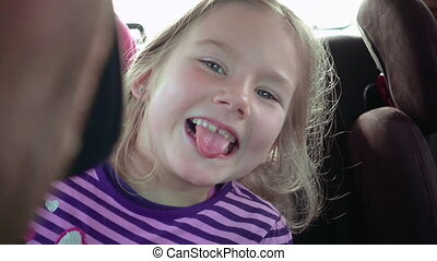 Little girl in a child car seat smiles and laughs