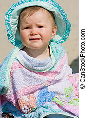 little girl in a colorful towel on the beach