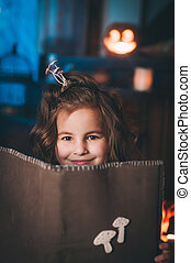 Little girl in a costume of witch with magic book