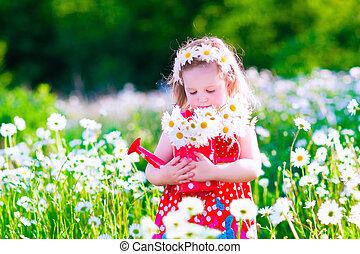 Little girl in a daisy flower field - Kid gardening. Little...