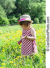 little girl in a hat on a glade with dandelions
