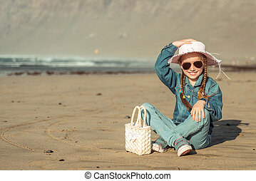 little girl in a hat on the  beach