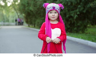 little girl in a knitted hat autumn