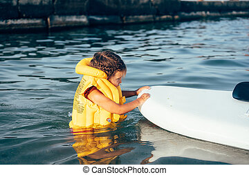 Little girl in a life jacket bathe in the sea.