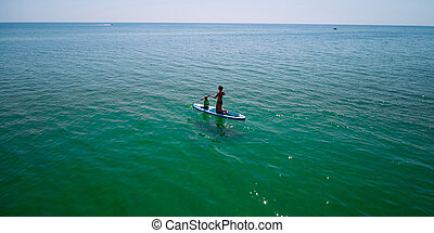 Little girl in a life vest sitting on the paddle board with mother