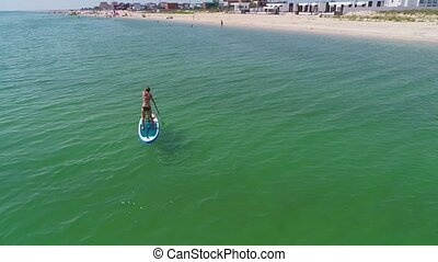 Little girl in a life vest sitting on the paddle board with mother.