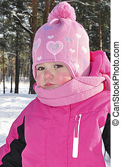 Little girl in a pine forest in winter.