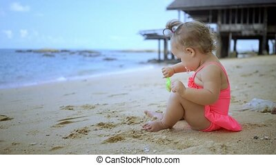 little girl in a pink bathing suit playing with sand on the shore of the blue sea. concept of happy childhood, fashion, holidays.