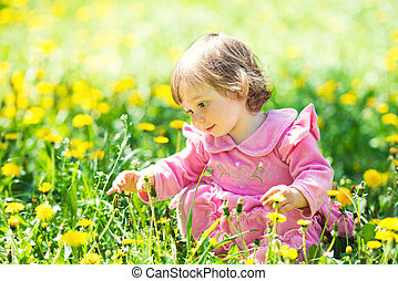 little girl in a pink dress is looking at a dandelion in a green clearing.