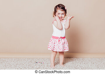little girl in a pink dress laughter smile