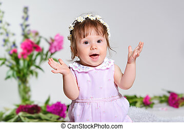 Little girl in a pink dress sitting with a bouquet of pink flowers