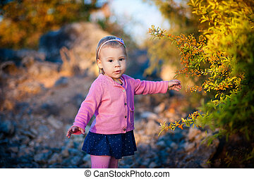 little girl in a pink jacket touch pen orange berries on the bush.