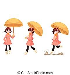 Little girl in a raincoat with umbrella enjoying rainy weather