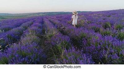 Little girl in a straw hat walks the field of lavender in slow motion