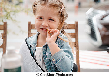 Little girl in a street cafe with french fries