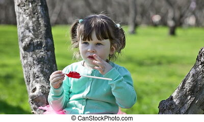 little girl in a turquoise jacket eats sugar candy, sitting on a tree