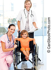 Little girl in a wheelchair doctors looking at the camera