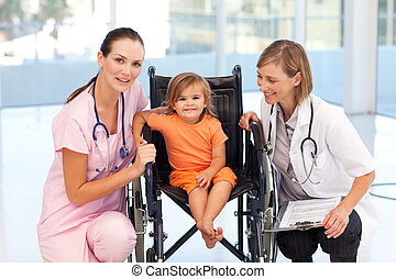 Little girl in a wheelchair with nurse and doctor